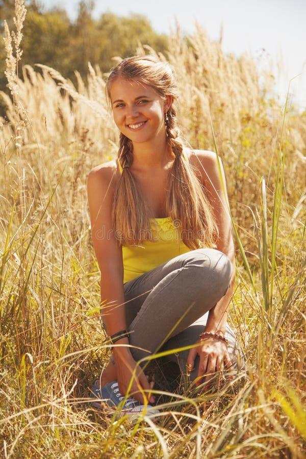 O retrato da menina feliz bonita na grama do sol, verão, cura fotografia de stock royalty free