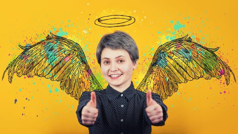 O retrato da menina feliz mantém os polegares acima sobre o fundo amarelo, sorrindo amplamente imaginando-se um anjo com asas mac imagem de stock