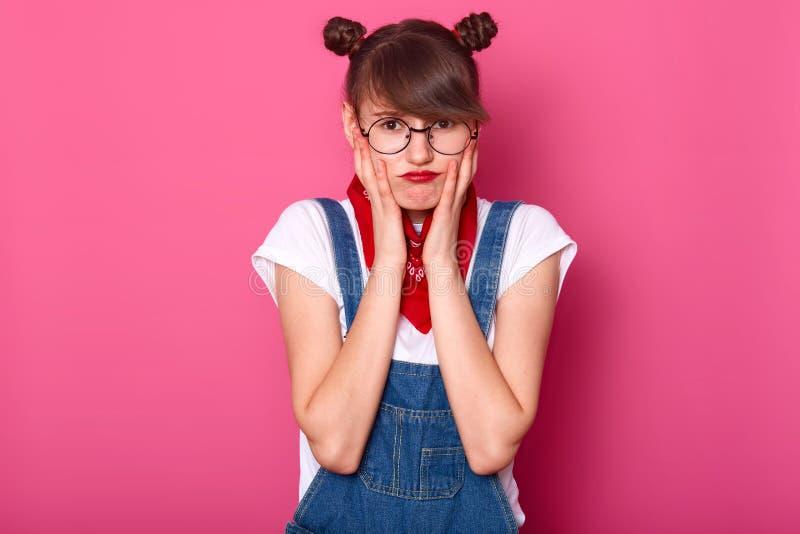 O retrato da menina infeliz offened do adolescente com bordos pouty, mantém as mãos nos mordentes, desagradados com tudo, sente-a fotos de stock