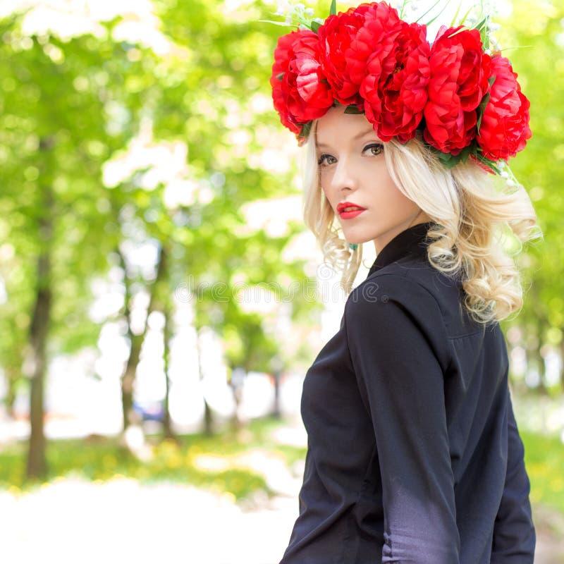 O retrato da menina loura 'sexy' bonita com uma grinalda da peônia anda no jardim em um dia ensolarado imagem de stock