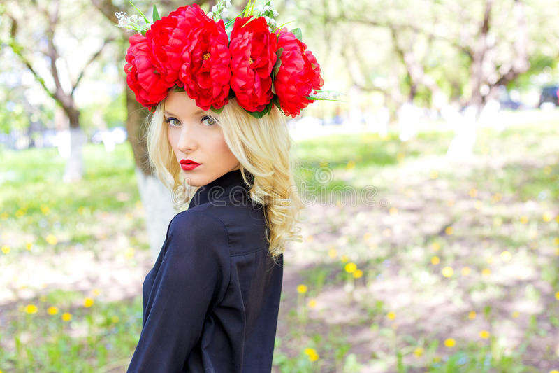 O retrato da menina loura 'sexy' bonita com uma grinalda da peônia anda no jardim em um dia ensolarado fotografia de stock royalty free