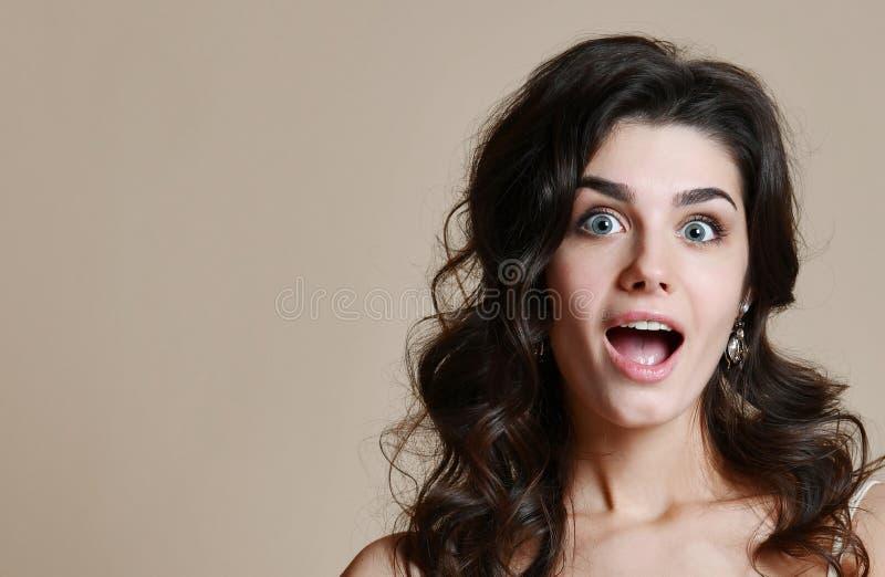O retrato da menina moreno surpreendida, mantém a boca abriu largamente, imagens de stock