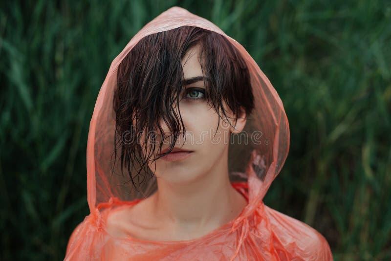 O retrato da menina na capa de chuva vermelha sob a chuva imagens de stock royalty free