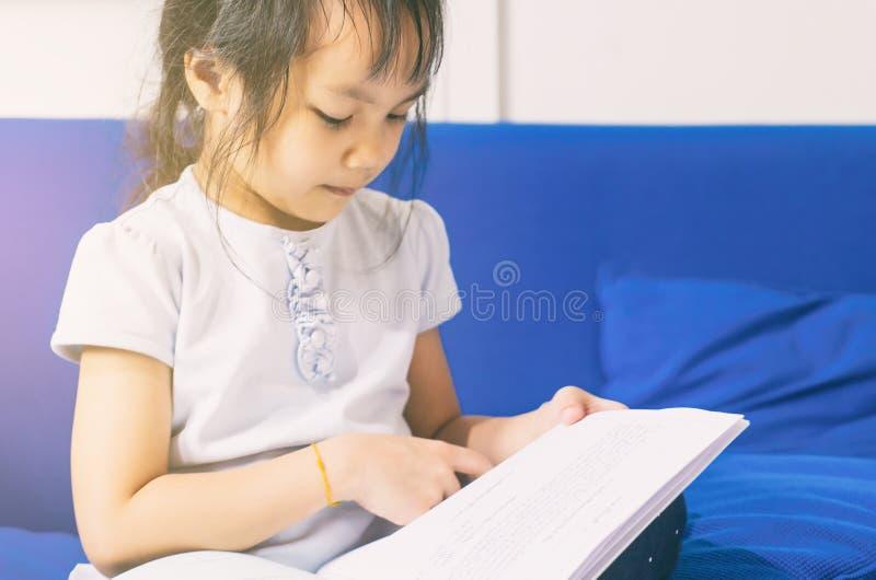 O retrato da menina Nerdy asiática está lendo um livro imagem de stock