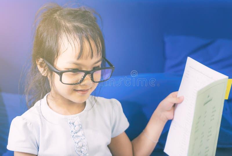 O retrato da menina Nerdy asiática está lendo um livro imagens de stock