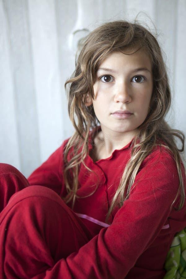 O retrato da menina sonolento nova onze anos velha nos pyjamas vermelhos que sentam-se na cama imagens de stock