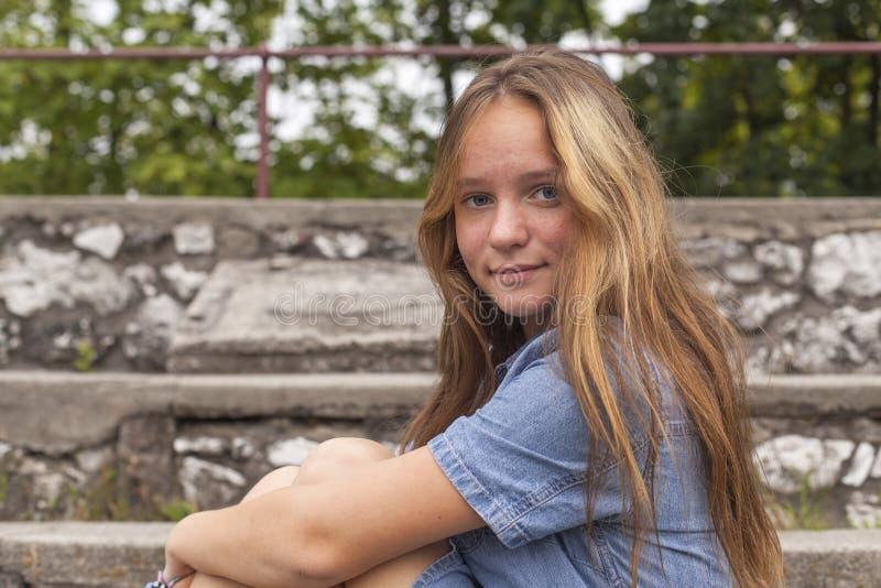 O retrato da moça que senta-se na pedra pisa no parque velho da cidade caminhada foto de stock royalty free