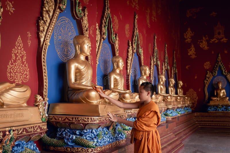 O retrato da monge pequena do principiante está limpando a estátua da Buda em um conceito do templo, da religião e da adoração imagens de stock