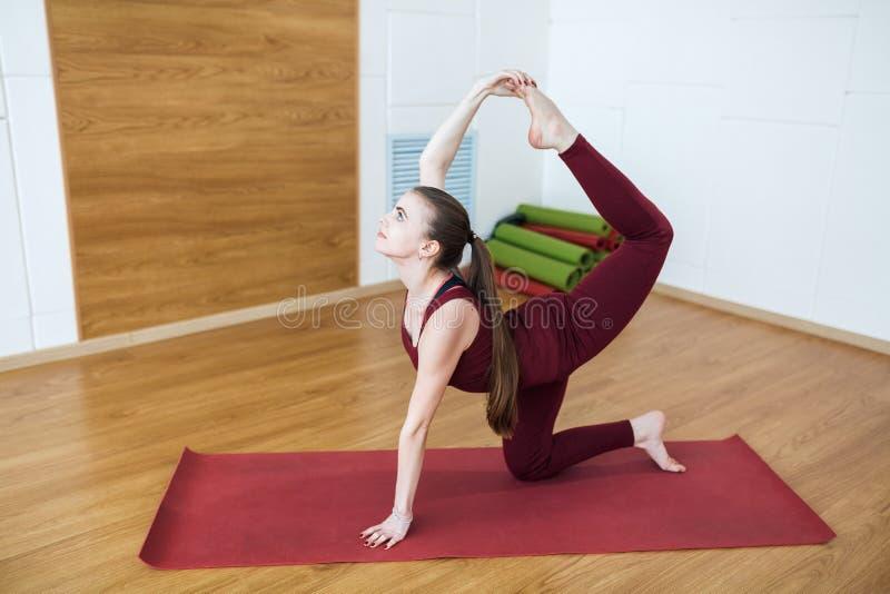 O retrato da mulher apta dos jovens bonitos em um terno vermelho que faz o esporte exercita no companheiro vermelho no gym, varia imagem de stock