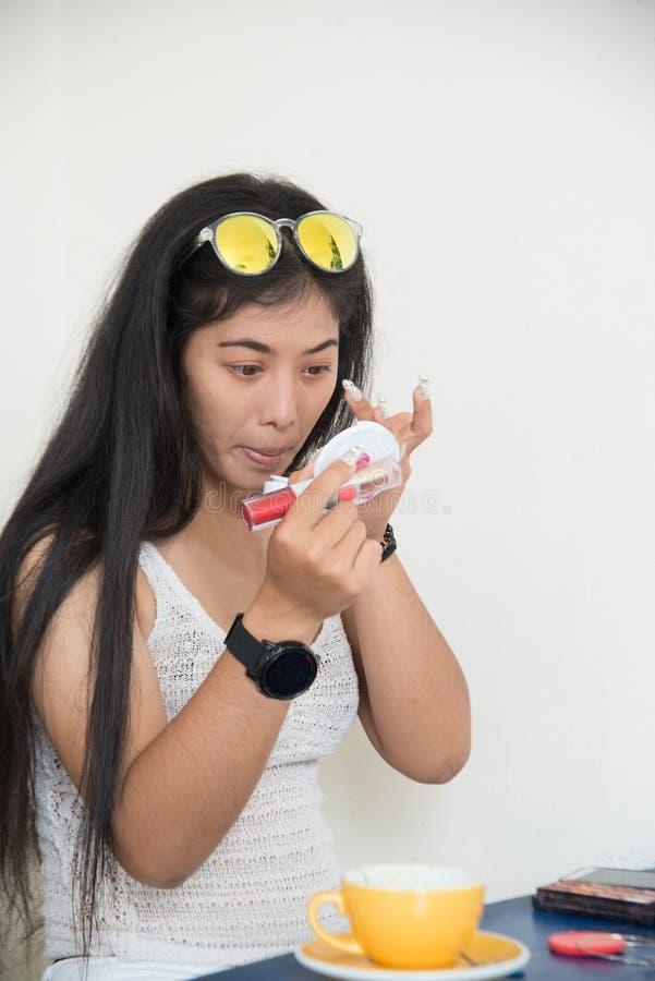 O retrato da mulher asiática bonita aplica-se para compor a sombra para os olhos com seus olhos e batom vermelho imagens de stock