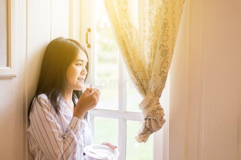O retrato da mulher asi?tica bonita est? guardando uma x?cara de caf? e est? olhando algo na janela em casa na manh?, feliz e no  fotos de stock royalty free