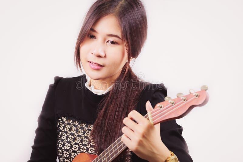 O retrato da mulher asiática nova aprecia jogar a guitarra, isolada sobre fotografia de stock royalty free