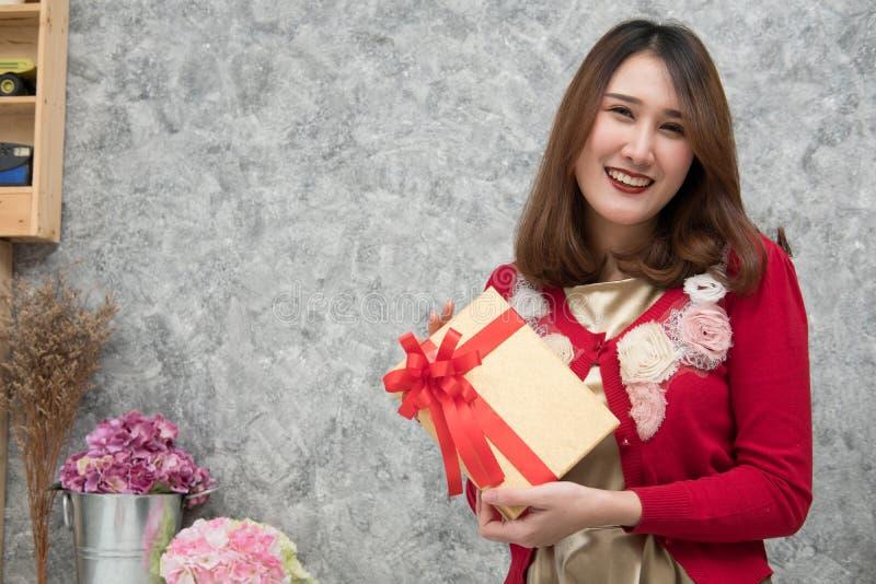 O retrato da mulher asiática senta-se em casa menina com a caixa do presente do presente foto de stock