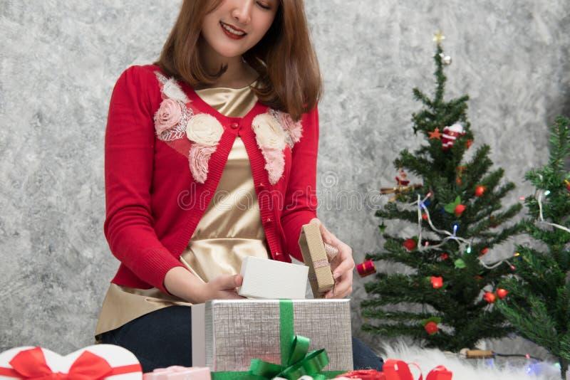 O retrato da mulher asiática senta-se perto da árvore de Natal em casa Wi da menina imagem de stock royalty free
