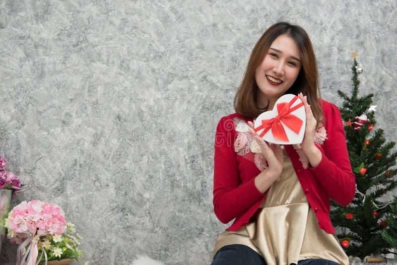 O retrato da mulher asiática senta-se perto da árvore de Natal em casa Wi da menina imagens de stock