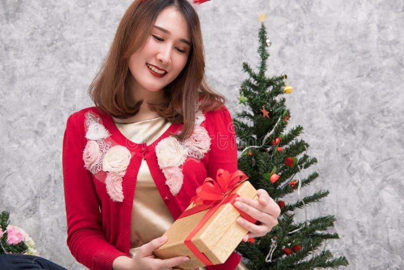 O retrato da mulher asiática senta-se perto da árvore de Natal em casa Wi da menina foto de stock royalty free
