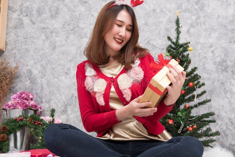 O retrato da mulher asiática senta-se perto da árvore de Natal em casa Wi da menina imagens de stock royalty free