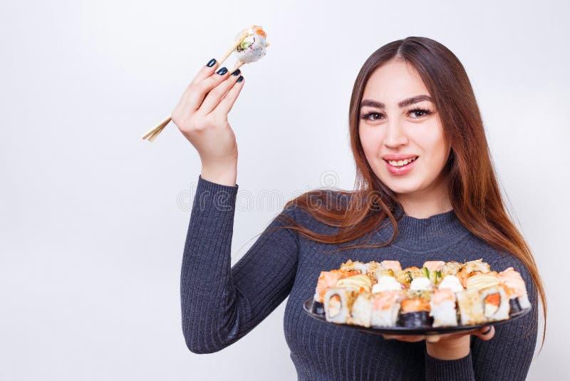 O retrato da mulher atrativa nova com rolos de sushi ajustou-se, estúdio imagens de stock