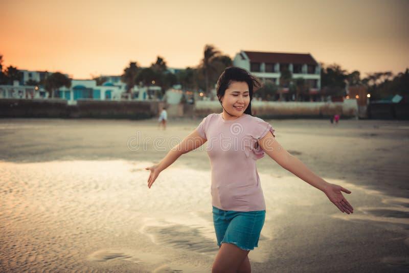 O retrato da mulher bonita é de apreciação e de relaxamento na praia no tempo de férias, emoção asiática da felicidade da menina  imagens de stock royalty free