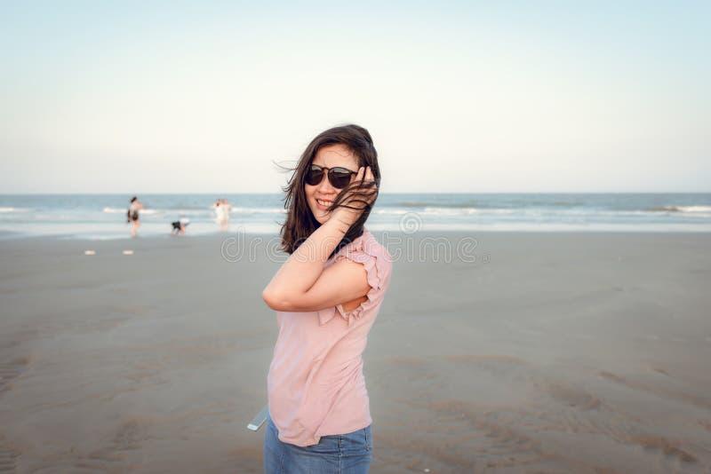 O retrato da mulher bonita ? de aprecia??o e de relaxamento na praia no tempo de f?rias, emo??o asi?tica da felicidade da menina  fotos de stock