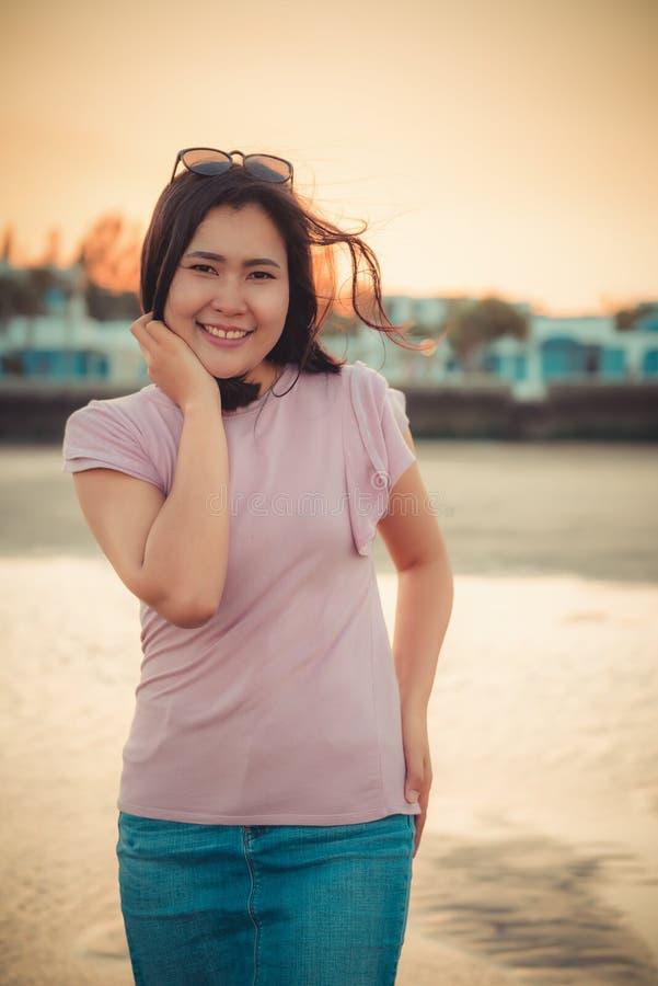 O retrato da mulher bonita ? de aprecia??o e de relaxamento na praia no tempo de f?rias, emo??o asi?tica da felicidade da menina  imagem de stock royalty free