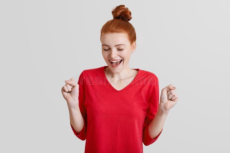 O retrato da mulher bonita do gengibre aperta os punhos, sucesso dos rejoces, vestido na camiseta vermelha, isolada sobre o fundo fotos de stock