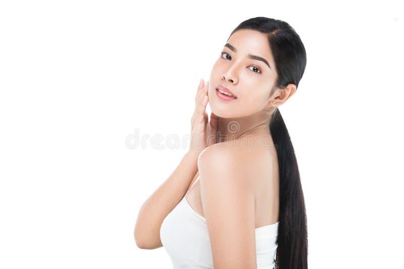 O retrato da mulher bonita dos cuidados com a pele aprecia e feliz, tocando em sua cara fotografia de stock