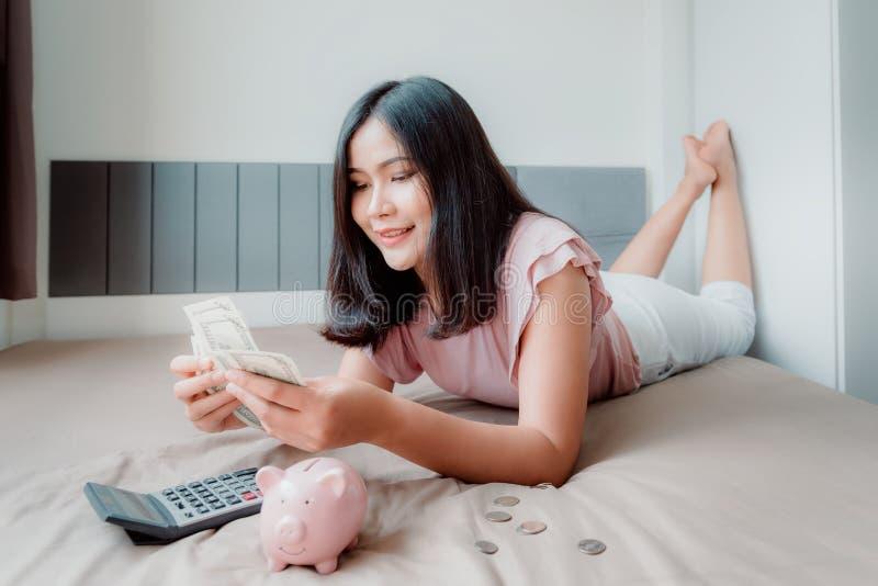 O retrato da mulher bonita está calculando a economia do dinheiro ao encontrar-se em seu quarto Negócio financeiro e conceito do  imagens de stock royalty free