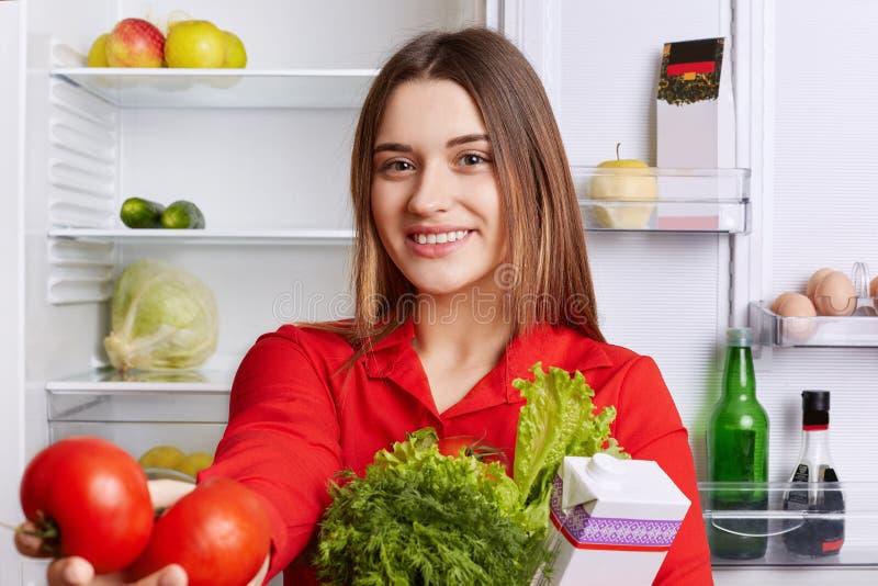 O retrato da mulher bonita feliz com expressão alegre vestiu-se na blusa vermelha, guarda legumes frescos, demonstra tomates verm fotos de stock royalty free