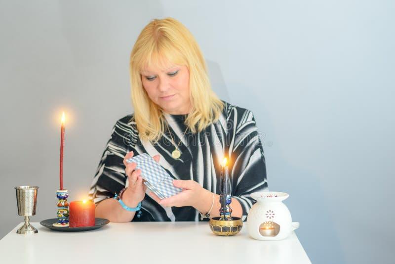 O retrato da mulher bonita da Idade Média senta-se perto de uma mesa do caixa de fortuna com os cartões e as velas de tarô imagem de stock royalty free