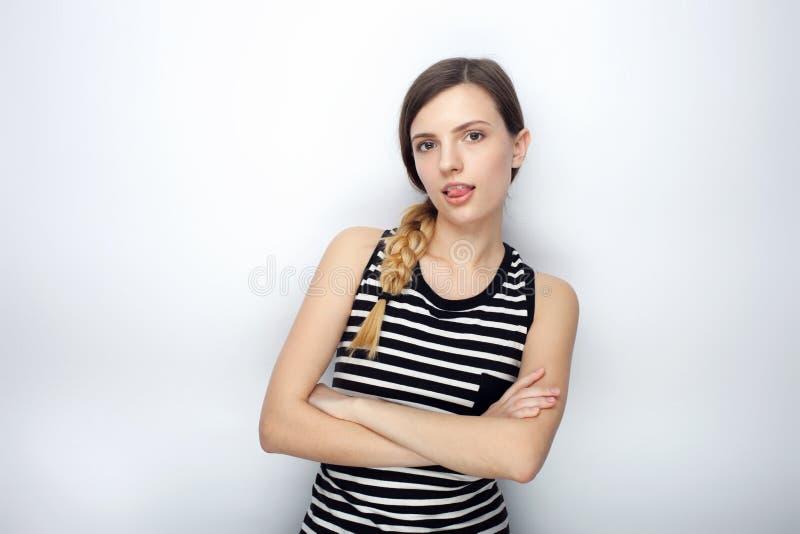 O retrato da mulher bonita nova impertinente em camisa listrada cruzou as mãos que mostram a língua que levanta para os testes mo foto de stock