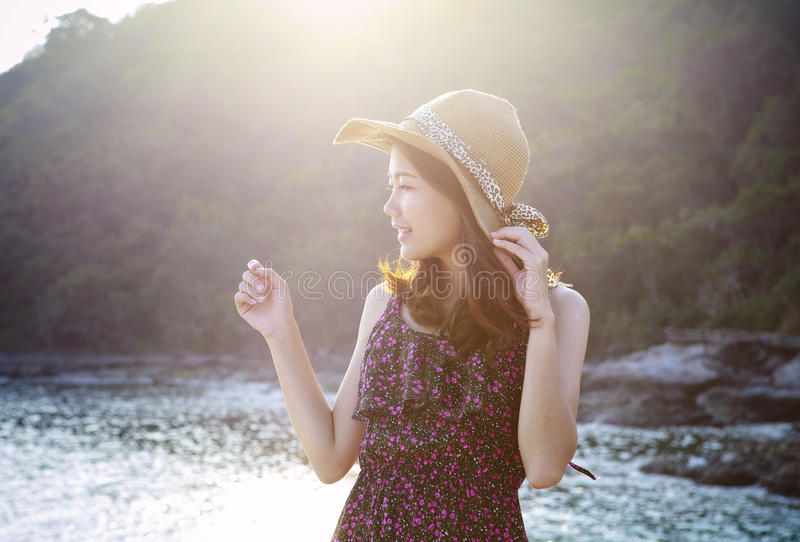 O retrato da mulher bonita nova que veste o vestido longo e o chapéu de palha largo que sorri no uso do lugar do lado de mar para foto de stock