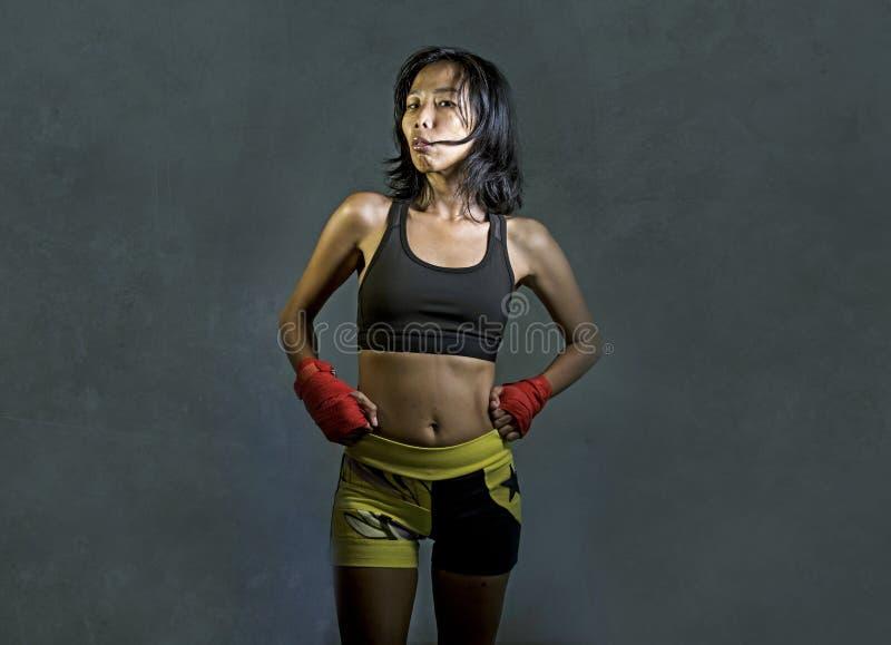 O retrato da mulher chinesa asiática do lutador desportivo e apto que usa os envoltórios do pulso que treinam o Muttahida Majlis- foto de stock
