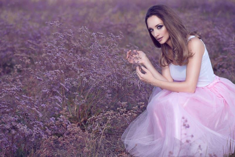 O retrato da mulher chique com provocante compõe e cabelo longo que senta-se no campo das flores violetas fotografia de stock royalty free