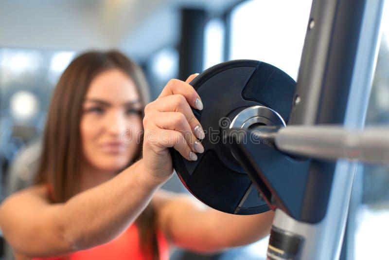 O retrato da mulher considerável põe a placa do peso sobre o barbell no gym fotografia de stock