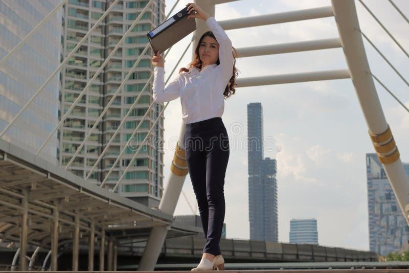 O retrato da mulher de negócio asiática atrativa nova aumentou o dobrador do original para a luz solar de proteção no fundo exter foto de stock royalty free