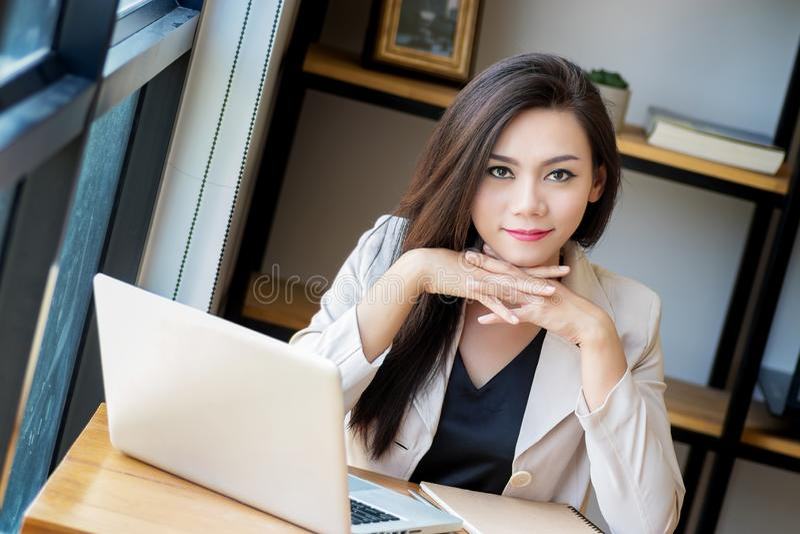 O retrato da mulher de negócio asiática bonita e segura na idade propícia para o trabalho que usa a tecnologia do portátil do com imagem de stock royalty free
