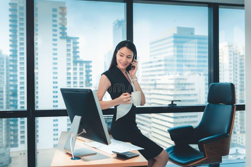 O retrato da mulher de negócio está falando no telefone celular em seu escritório , Bonito da mulher asiática está chamando a alg foto de stock royalty free