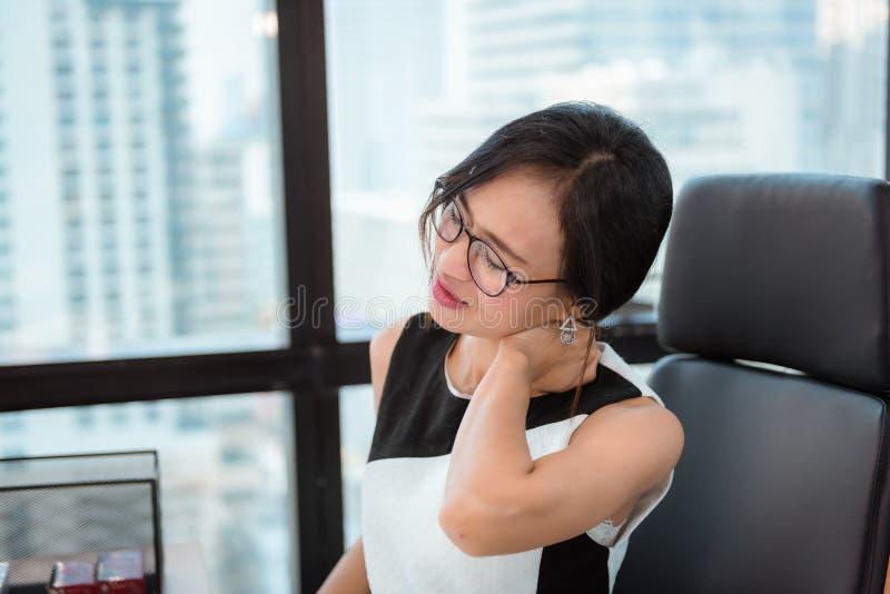 O retrato da mulher de negócio que tem a dor do ombro durante o trabalho no local de trabalho do escritório, mulher asiática está imagem de stock royalty free