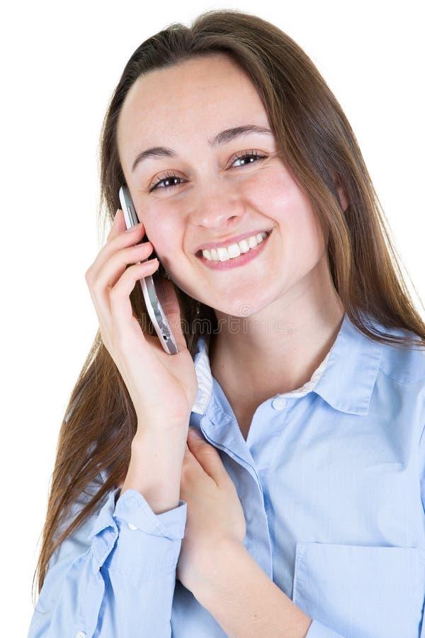 O retrato da mulher de negócios bonita nova de sorriso na roupa azul da camisa fala no telefone celular no fundo branco imagens de stock royalty free