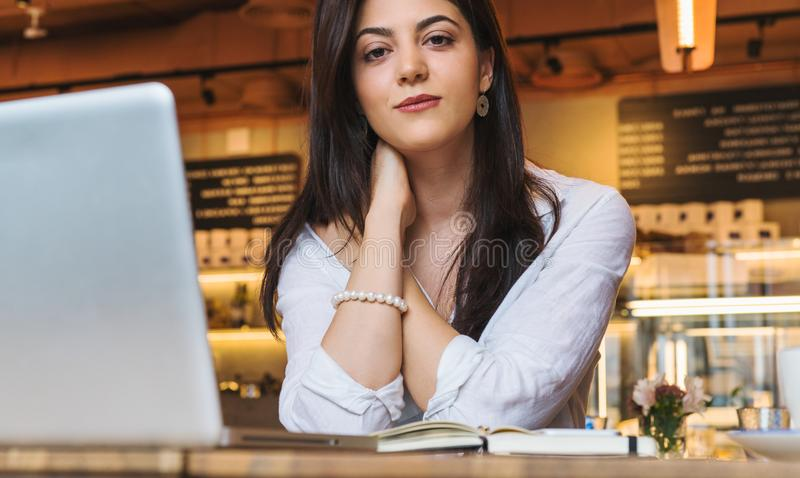 O retrato da mulher de negócios nova, estudante, vestiu-se na blusa branca, sentando-se na tabela no café na frente do computador fotografia de stock