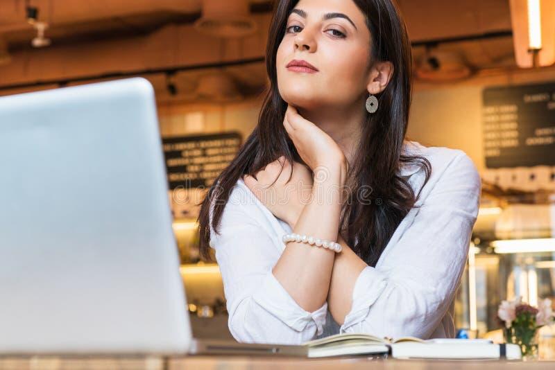 O retrato da mulher de negócios nova, estudante, vestiu-se na blusa branca, sentando-se na tabela no café na frente do computador fotografia de stock royalty free