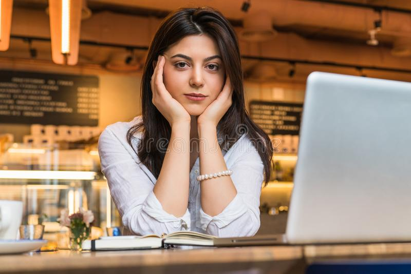 O retrato da mulher de negócios nova, estudante, vestiu-se na blusa branca, sentando-se na tabela no café na frente do computador fotos de stock
