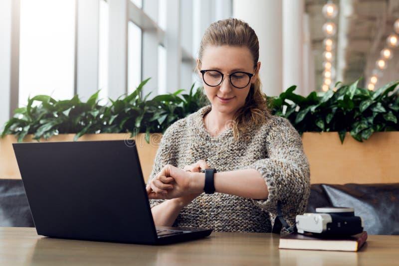 O retrato da mulher de negócios nova que senta-se no café, trabalhando no portátil, olha o relógio de pulso Mercado em linha, edu fotos de stock