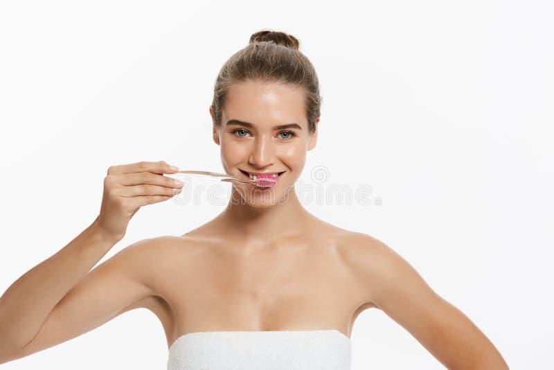 O retrato da mulher de sorriso caucasiano atrativa isolada no estúdio branco disparou em escovar seus dentes imagem de stock