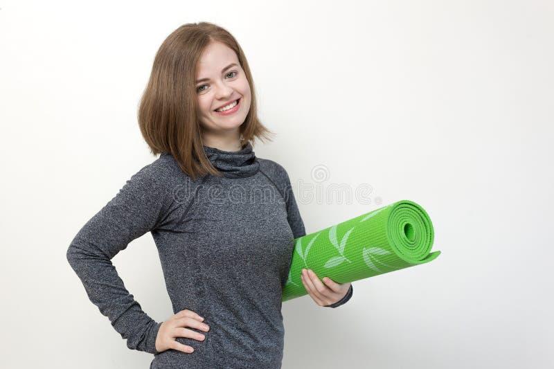 O retrato da mulher de sorriso da menina nos esportes veste guardar a esteira rolada da ioga que vai ao gym para dá certo ou exer imagens de stock