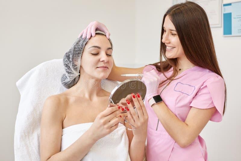 O retrato da mulher de sorriso que olha no espelho no armário do cosmetologist, tem a consulta com cosmetologist, wamts ter anti imagem de stock