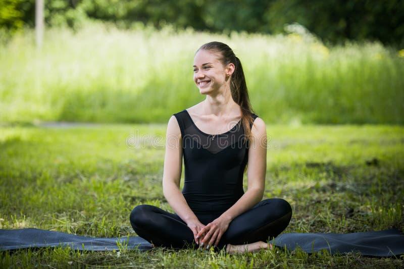 O retrato da mulher desportiva que faz o esticão exercita no parque antes de treinar Atleta fêmea que prepara-se para movimentar- foto de stock