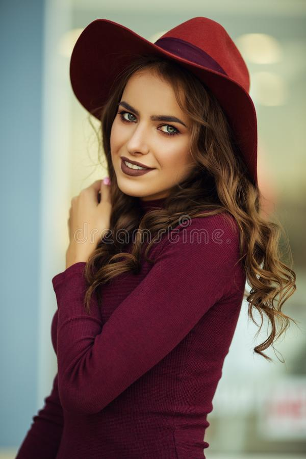 O retrato da mulher elegante bonita está vestindo a roupa do outono da forma e o chapéu vermelhos na frente da loja-janela fotografia de stock royalty free