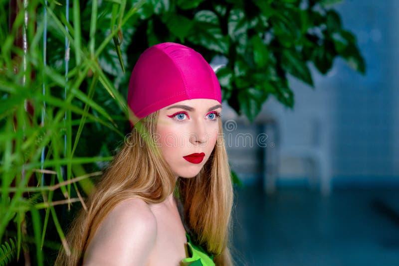 O retrato da mulher loura atrativa bonita atlética com compõe no tampão e no terno da nadada na piscina fotografia de stock royalty free